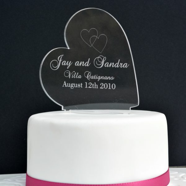 "Clear Acrylic Heart Cake Topper shows a black background and a white iced cake with a pink ribbon wrapped around the bottom. On top of the cake stands a glass like sideways heart engraved with two intertwined hearts and the words ""Jay and Sandra Villa Catignano August 12th, 2010"". Engraved personalised cake topper by Precision Designs in Ireland"