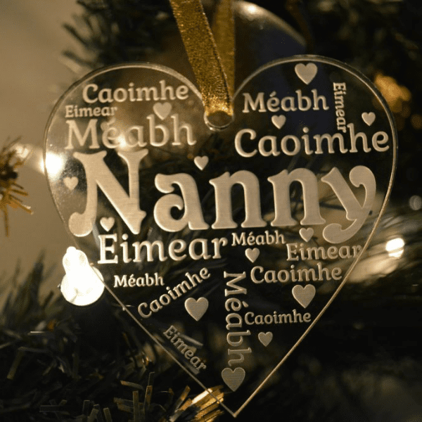 Grandparent Christmas Ornament features a clear acrylic glass-like heart ornament, see through with the word Nanny in the centre and first names surrounding it with little hearts dotted throughout engraved or etched appearing in white writing. Hanging from a gold glittery ribbon with a Christmas tree and lights in the background.