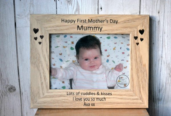 "First Mother's Day Photo Frame, First Mother's Day Photo Frame, brown wooden photo frame in landscape position and a picture of a smiling baby girl in it. It reads ""Happy First Mother's Day Mummy, lots of cuddles and kisses, I love you so much, Ava xx"" by laser engraving business Precision Designs, laser engraved gifts Ireland"