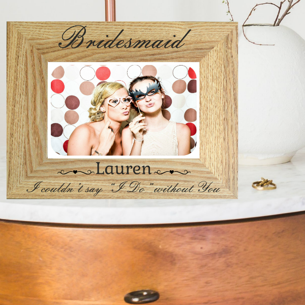 "Birdesmaid Photo Frame shows a brown photo frame in landscape orientation on a bed side locker. Showing 2 female friends in party clothes in the frame engraved with ""Bridesmaid Lauren I couldn't say I do without you"". A laser engraved bridesmaid proposal gift by Precision Designs made in Ireland"