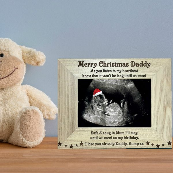 Christmas Baby Scan Photo Frame, merry christmas daddy photo frame from bump, a brown wooden engraved photo frame on a sideboard against a blue wall standing beside a teddy bear with a baby scan photo insert. Baby in the scan is wearing a red and white santa hat by Precision Designs Ireland