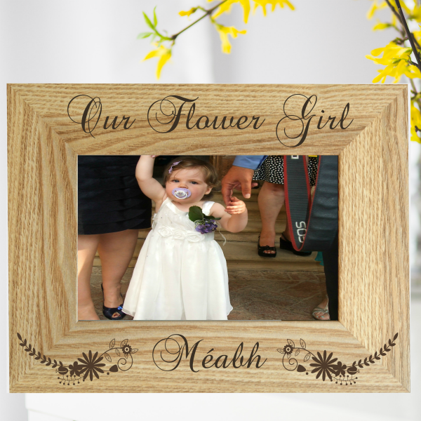"Flower girl Photo Frame shows a brown wooden frame in landscape orientation against a white background with yellow flowers. In the frame there is a picture of a little girl circa 1 year old in a white dress with a purple coursage and the laser engraved message reads ""Our Flower Girl Méabh"" with decorative flowers engraved either side of the word ""Méabh"", Personalised gift by Irish business Precision Designs"
