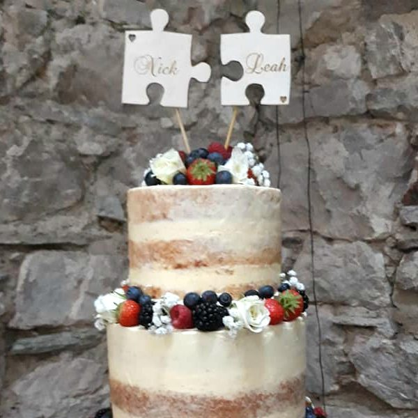 Jigsaw Cake Topper shows two puzzle pieces laser cut from birch plywood, Engraved with the names Nick and Leah and standing on top of a naked style wedding cake decorated with butter icing and fresh fruit against a natural stone background. This rustic cake topper was laser engraved by Precision Designs in Ireland