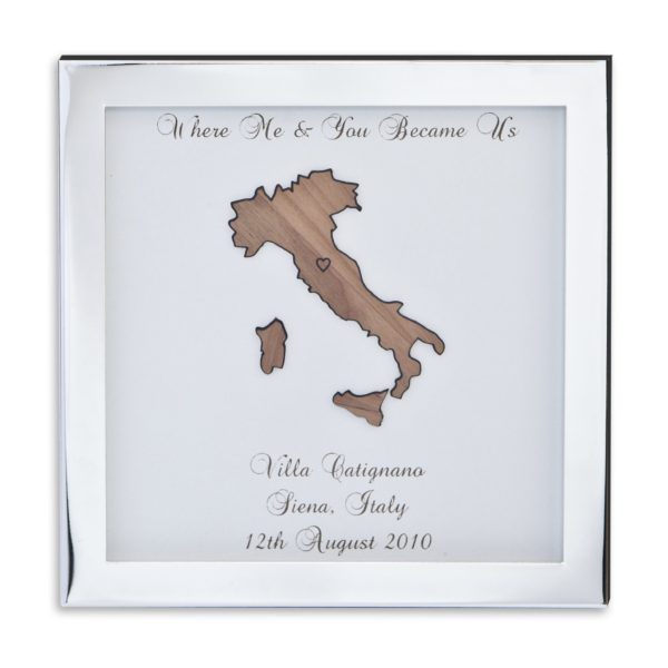 "Where me and you became us shows a silver frame against a white background. Inside the frame is a white board engraved with ""Where me and you became us, Villa Catignano, Sienna, Italy, 12th August 2010"" an a laser cut wooden outline of Italy and Sicily. Personalised wedding gift by Precision Designs ireland"