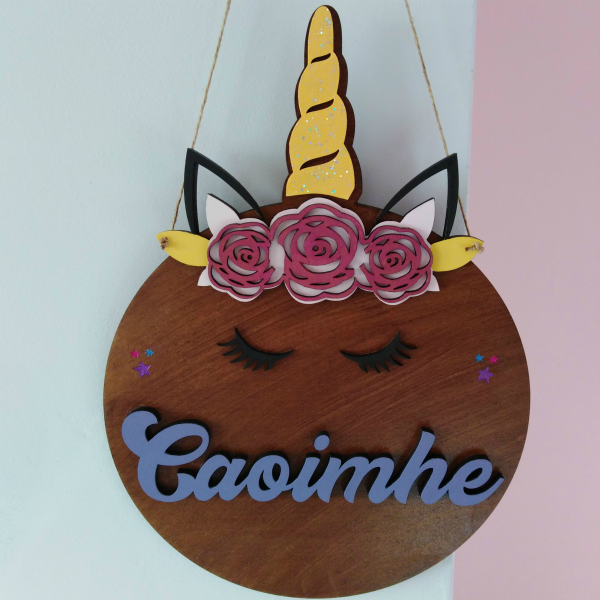 "Unicorn name plaque, a wooden sign in the shape of a unicorn's head. Gold horn, black ears and eyelashes and pink roses crown. With the name ""Caoimhe""in purple lettering Hanging from a jute natural cord against a grey and pink backdrop. Personalised signs Ireland, Precision Designs. Unicorn, children's decor, chidlren's room signs, personalised name plaques"
