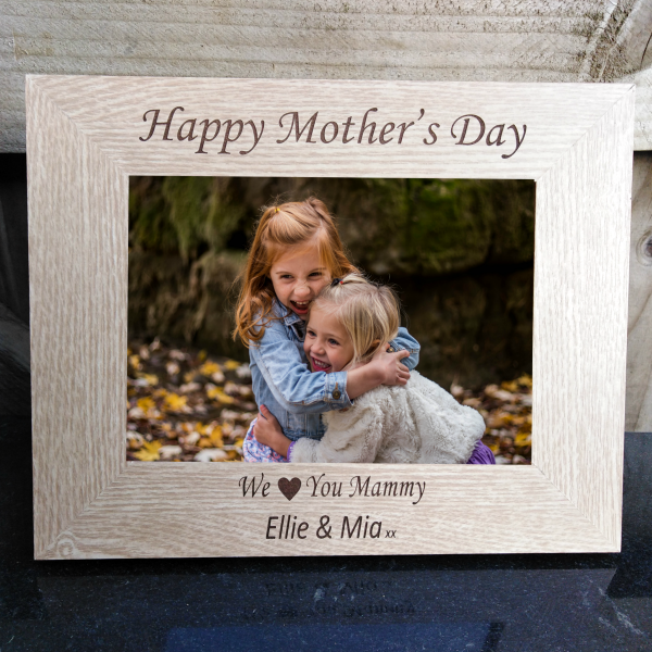 "Mother's Day Personalised Photo Frame, A light brown wooden photo frame with a picture of 2 girls in a happy embrace. Laser engraved and personalised, it reads ""Happy Mother's day, we Love you Mammy, Ellie & Mia,xx"". Mother's day gifts By precision Designs Ireland"