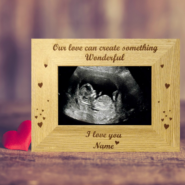 "Our love is Wonderful photo frame, a brown photo frame engraved with ""Our love can create something Wonderful, I Love You, Name"" and embellished with floating hearts on either side. Against a brown background . Laser engraved baby scan photo frame for Valentines Day Ireland. Valentines Day Gifts"