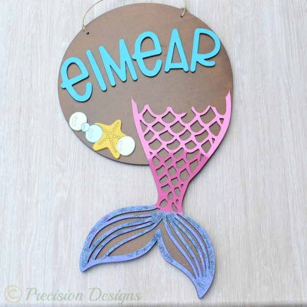 Mermaid name plaque, mermaid name sign, mermaid bedroom decor, a brown backing plaque decorated with laser cut hand painted lettering and mermaid tail detail. Name signs for kids bedroom, name signs for girls room